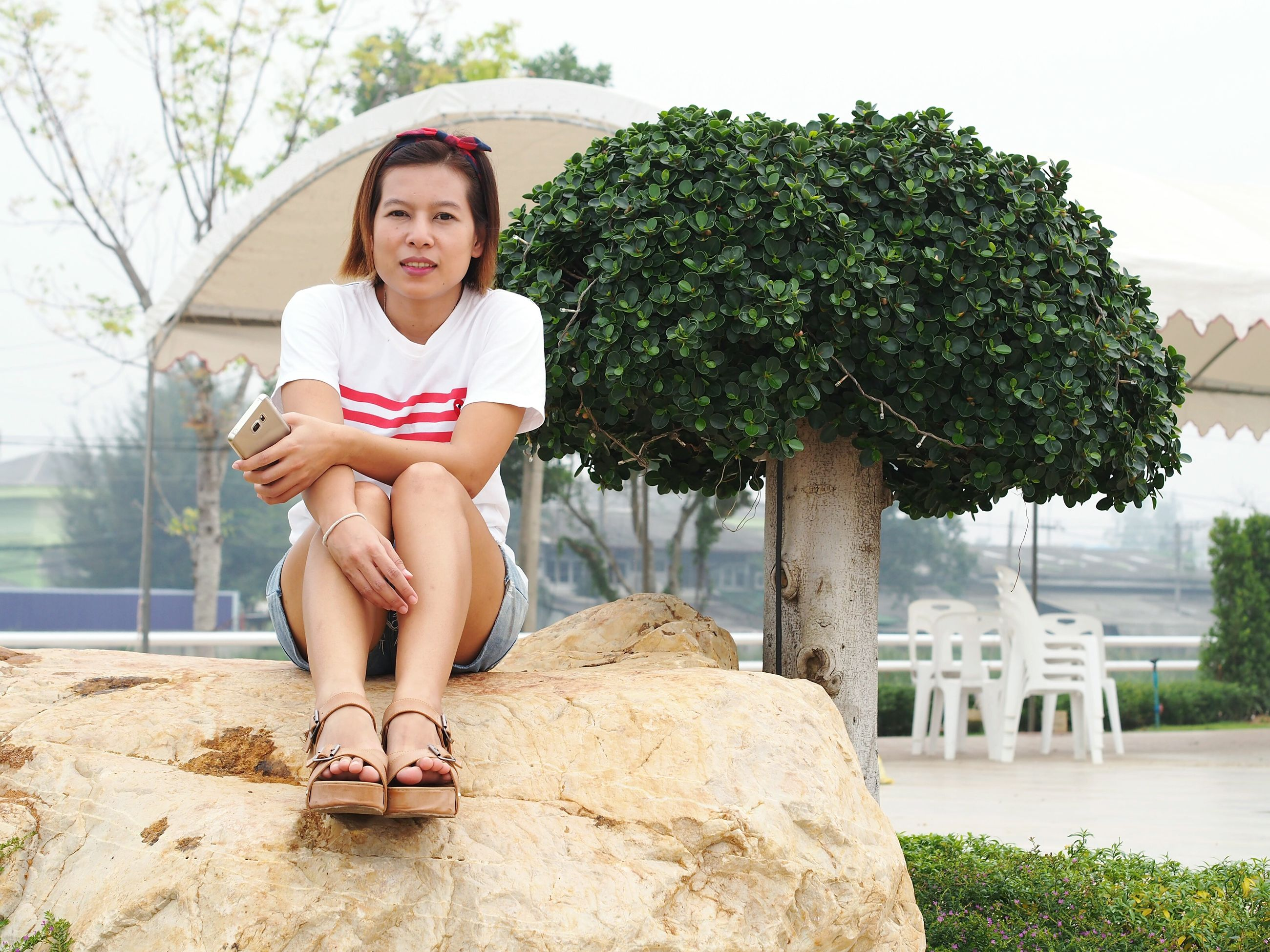 young adult, person, sitting, lifestyles, young women, leisure activity, full length, casual clothing, water, relaxation, tree, smiling, looking at camera, front view, portrait, happiness, standing, three quarter length