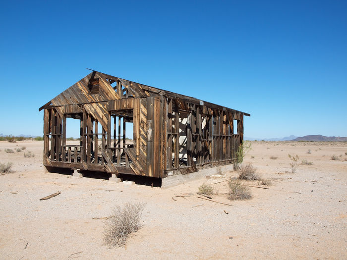 Abandoned Built Structure On Desert Against Clear Blue Sky