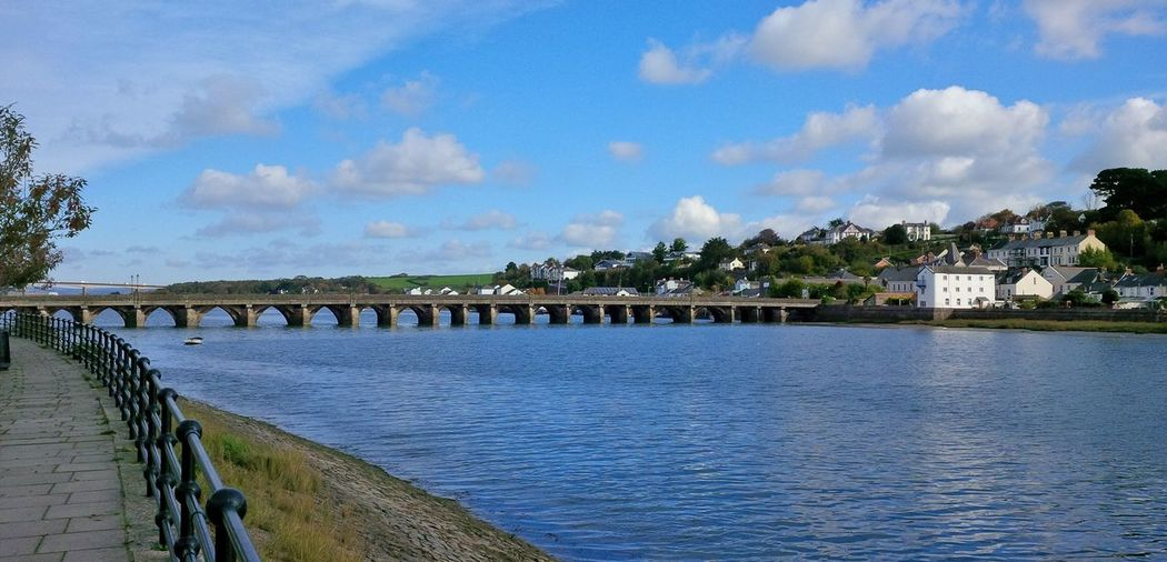 Bideford's medieval arched Long Bridge dates from 1474 & spans the River Torridge near its estuary and connects the East and West of the town - it is believed an original timber bridge was built in 1286 - This stone masonry bridge has 24 arches all of different sizes - the traditional explanation is that each arch was funded by a different local guild whilst another theory is that the piers of the arches were built on naturally existing and therefore randomly situated large stones in the river. - the River Torridge is the setting for the famous and much loved novel 'Tarka The Otter' by Henry Williamson. - In the C16th Bideford was Britain's third largest port and Sir Walter Raleigh landed his first shipment of tobacco here. Devon River Collection River View Riverside Arch Bridge Architecture Blue Bridge Bridge - Man Made Structure Building Building Exterior Built Structure Cloud - Sky Connection Medieval Medieval Architecture Outdoors River Riverbank Riverscape Riverside Photography Sky Torridgeside Water Waterfront