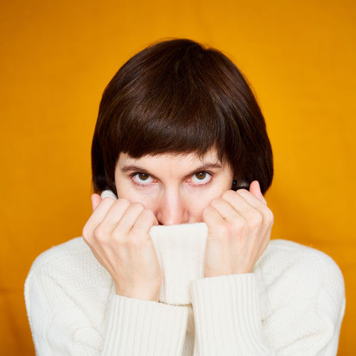 Portrait of young woman covering face against yellow background