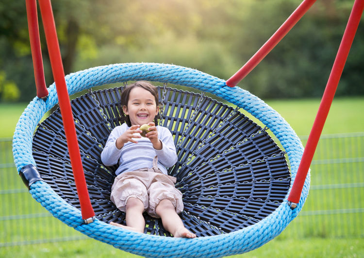Portrait of happy girl in swing at playground