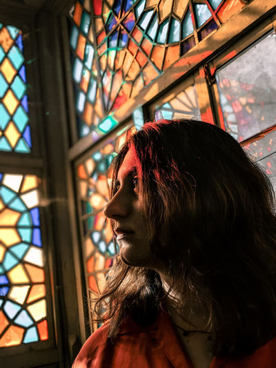 Young woman looking away while sitting against glass window
