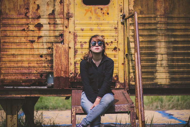 Portrait of young woman sitting against abandoned metal house