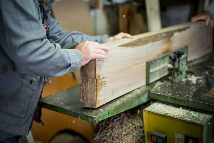 Midsection of carpenter cutting wooden plank at workshop
