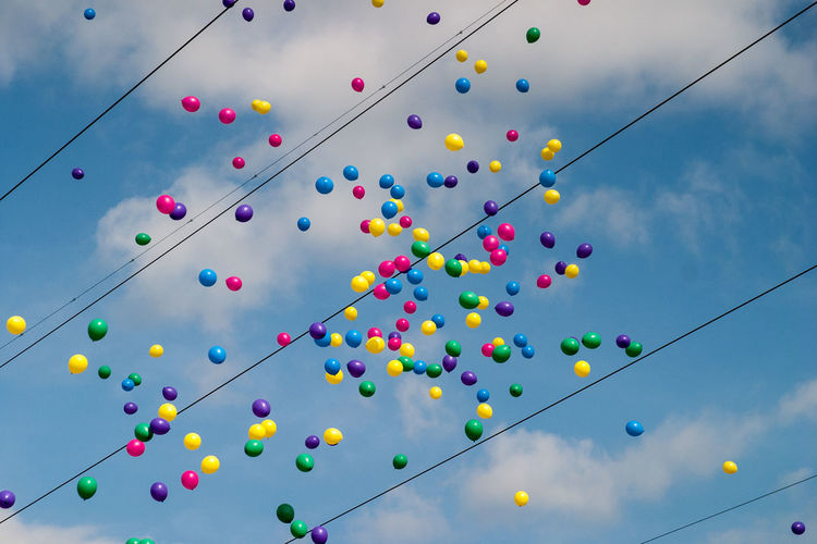 Low angle view of colorful helium balloons flying over cables against sky