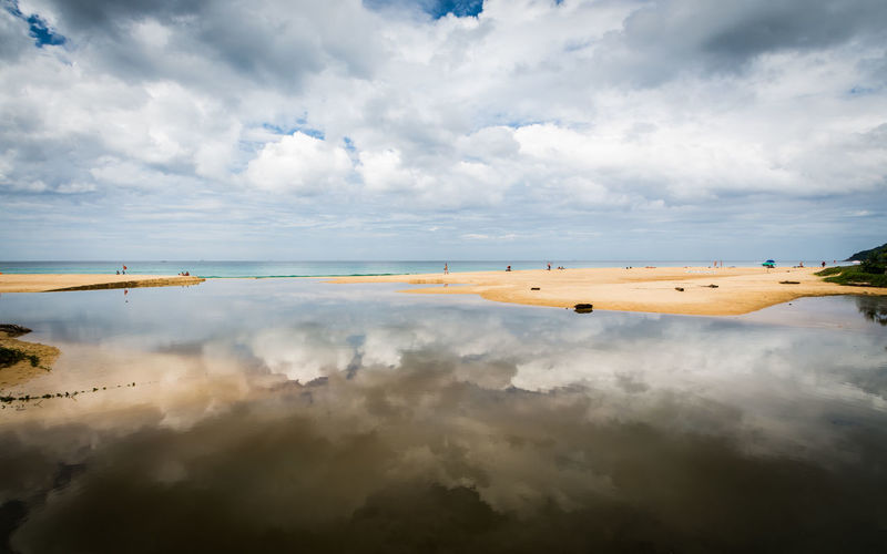Karon beach with cloudy blue sky reflect in the water, phuket, thailand