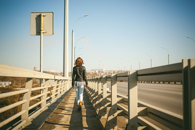 Rear view of young woman walking on bridge against sky