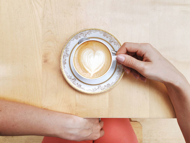 A woman's hand holding a cup of coffee on a wooden table seen from above. Architecture Beverage Cappuccino Coffee Coffee - Drink Coffee Break Coffee Cup Coffee Time Drink Drinking Enjoy Espresso Hand Heart Holding Latte Love Morning POV Refreshment Table Warm Women Wooden Young