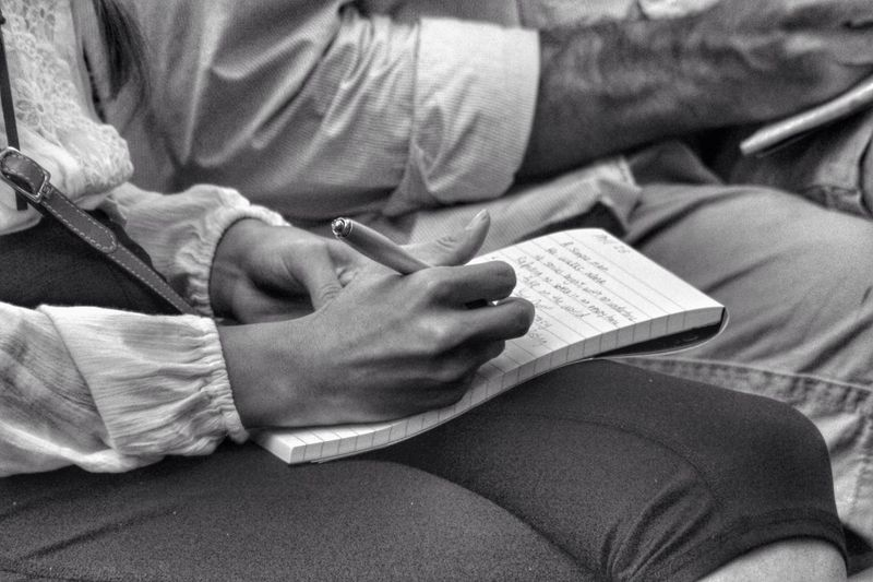 Midsection Of Woman Sitting By Man Writing On Book