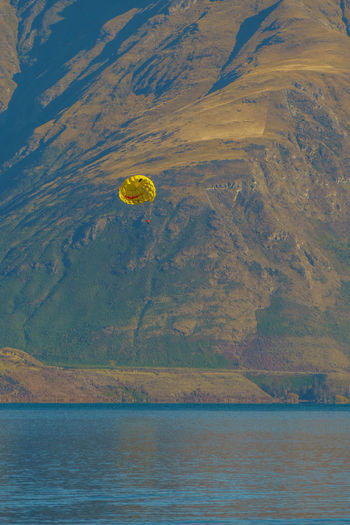 Distant view of person parasailing over sea against mountain
