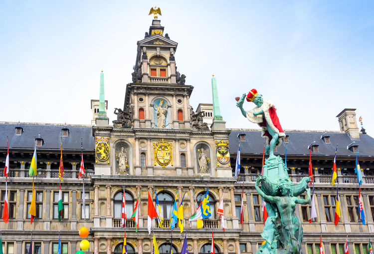 Low Angle View Of Brabo Fountain Against Antwerp City Hall At Grote Markt