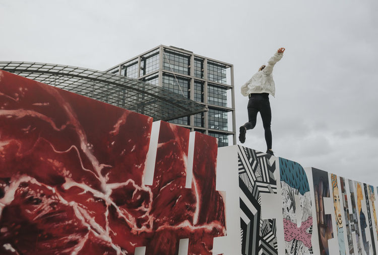Low Angle View Of Woman Balancing On Graffiti Wall Against Sky
