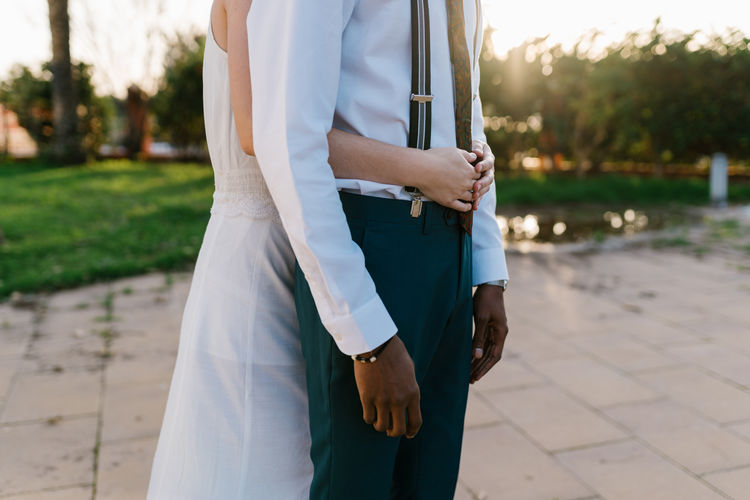 Midsection of couple standing outdoors
