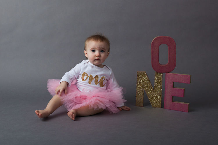 Baby Girl Sitting With Sparkling Text Over Gray Background