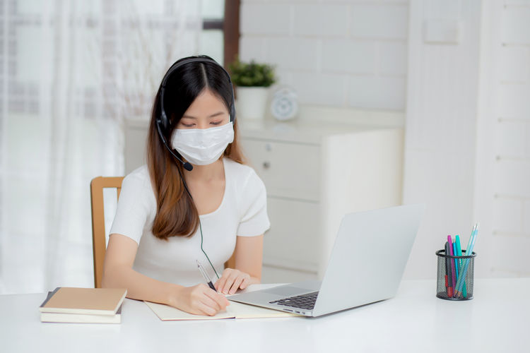 Young businesswoman wearing flu mask working in office