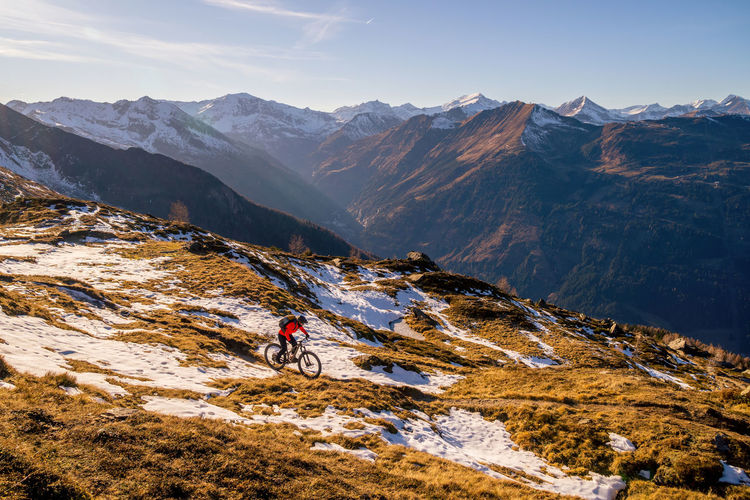 Woman riding a mountain bike on footpath in snow covered alpine terrain, gastein, salzburg, austria.