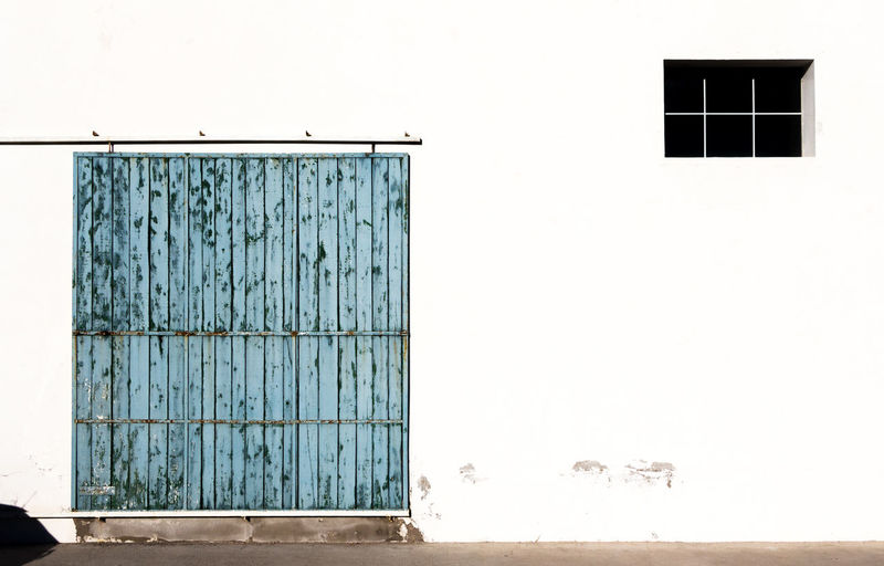 Closed door of building against clear sky