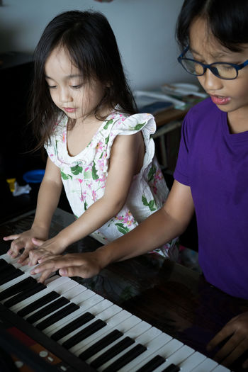 Happy kids playing piano at home