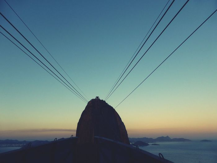 Low angle view of cables against clear sky during sunset