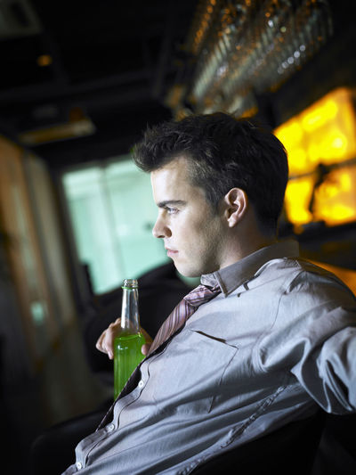 Side view of young businessman with drink at bar