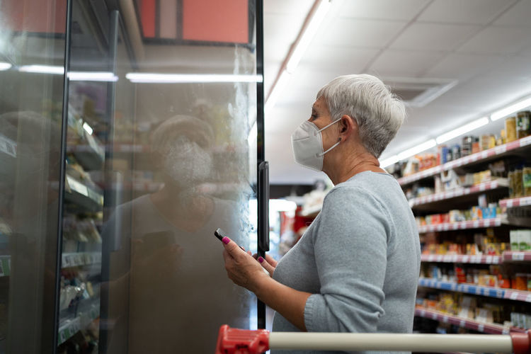Side view of woman standing by store