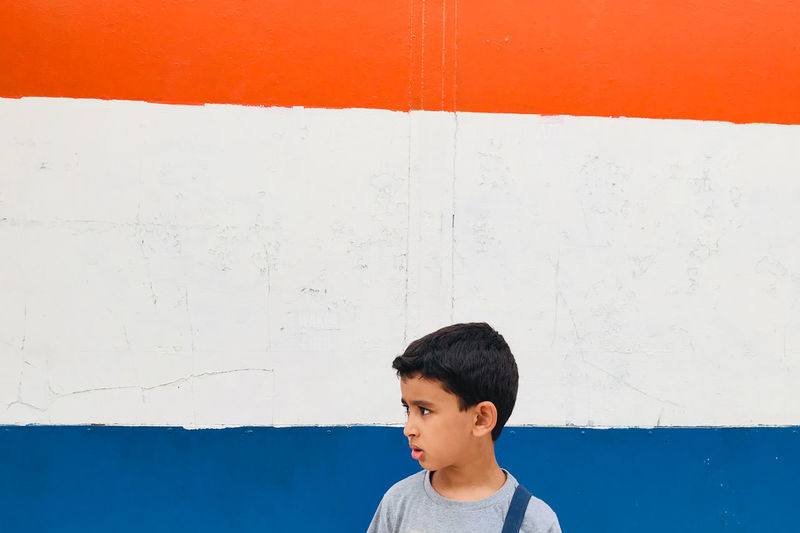 Thoughtful boy standing against painted wall