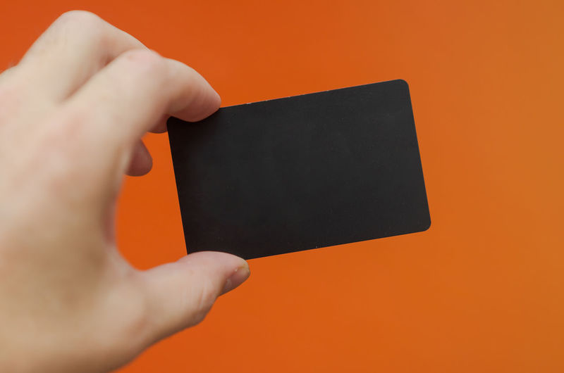 Close-up of person hand holding orange against colored background