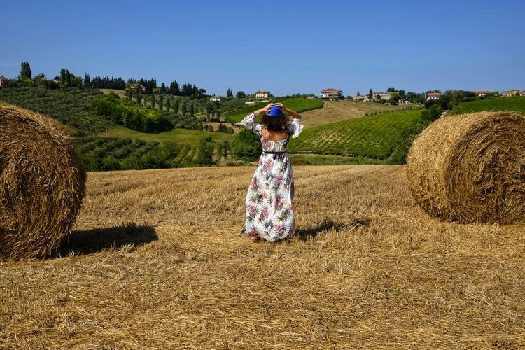 beautiful woman between round bales Freedom From Behind Woman Adult Agriculture Bale  Beauty In Nature Clear Sky Crop  Day Environment Farm Field Grass Hay Land Landscape Nature One Person Outdoors Plant Real People Rural Scene Sky