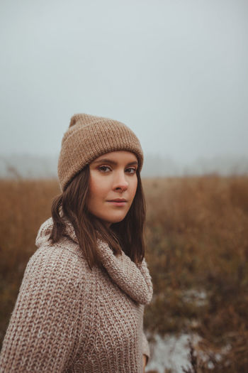 Portrait of woman standing in park against sky during winter