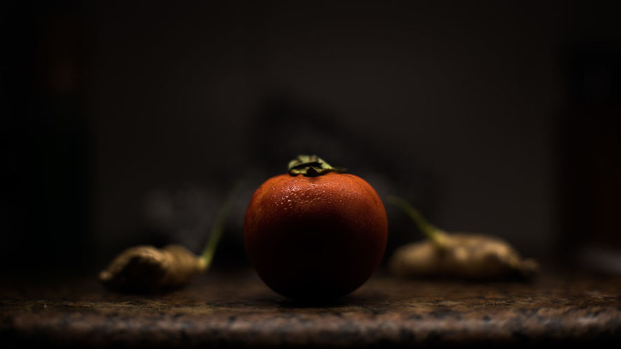 Close-Up Of Tomato With Gingers On Kitchen Counter At Home