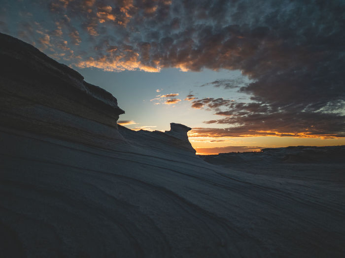 Low angle view of silhouette rock formations against sky during sunset
