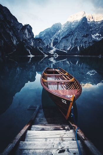Boat moored on calm lake against mountain during winter