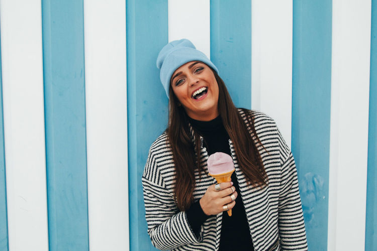 Portrait of cheerful woman having ice cream cone by striped wall