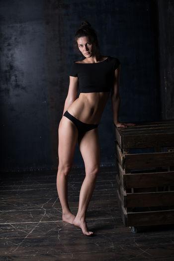 Portrait of beautiful woman wearing bikini standing by box