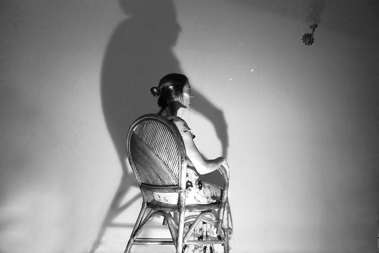 Low angle view of woman sitting on chair against wall