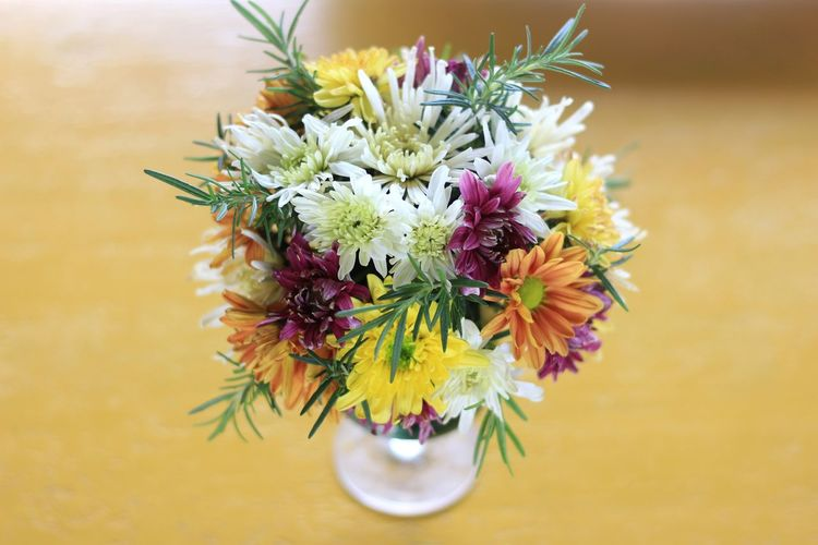 Flowers in vase on blurred blown table. Flower Bouquet Multi Colored Yellow Springtime Variation Uncultivated Vase Flowering Plant Wildflower Thistle Stamen Daisy Passion Flower Chrysanthemum Gerbera Daisy Dandelion Seed Single Flower Pistil Hibiscus Day Lily Crocus Petal Focus Blossom Botany Apple Blossom In Bloom Plant Life Lily
