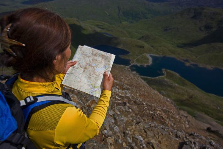 Woman holding umbrella on mountain