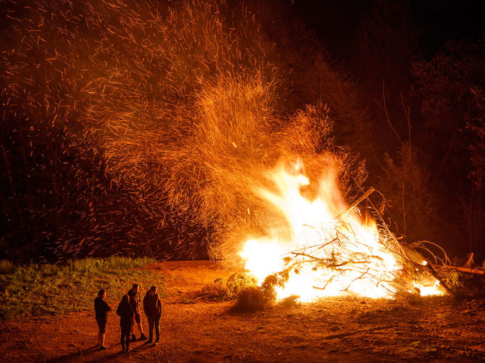 People by bonfire on field at night