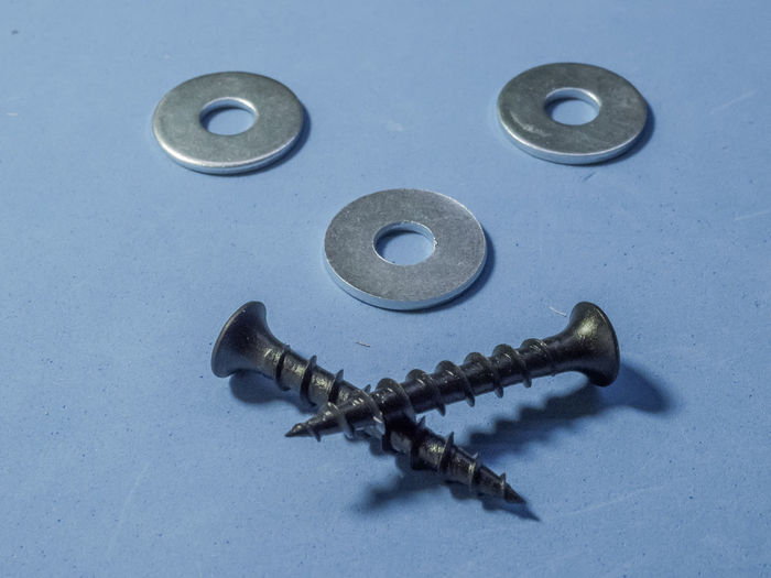 High angle view of screws on blue background
