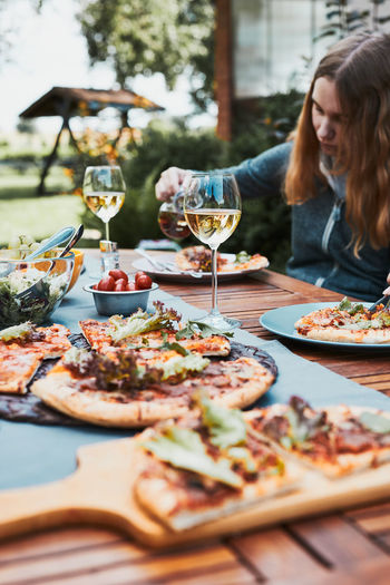 Family and friends having meal - pizza, salads, fruits and drinking white wine during summer picnic