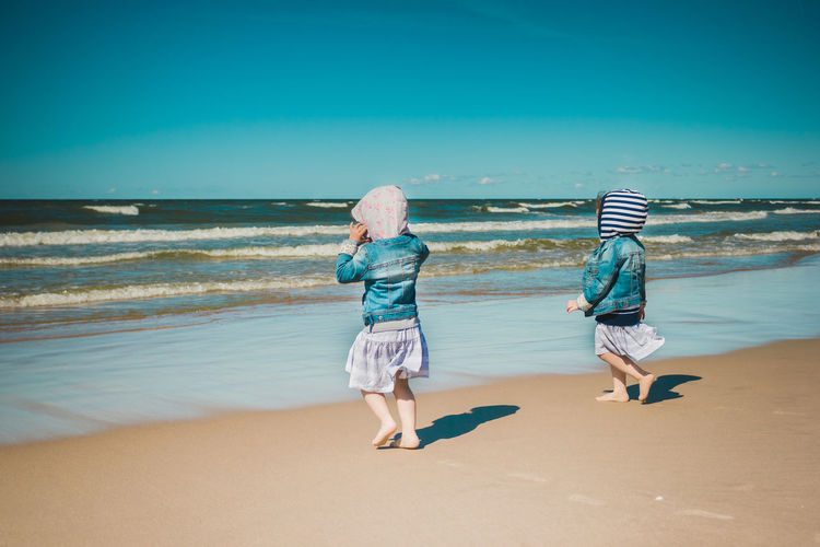 Full length of siblings walking at beach against sea and sky