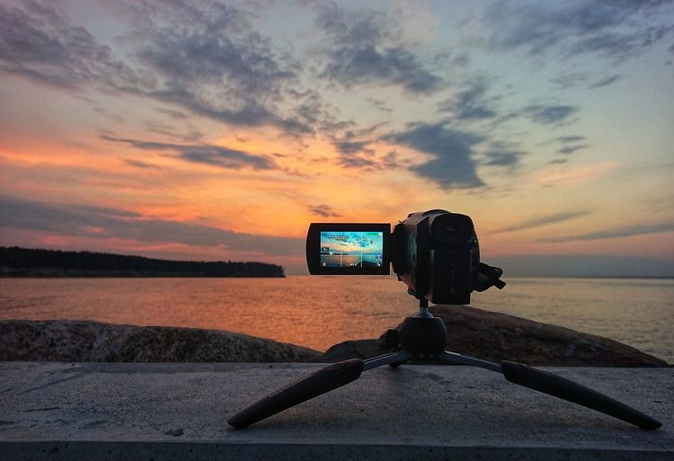 Camera on tripod by sea against sky during sunset