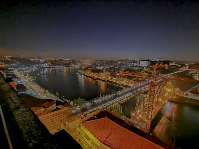 High angle view of illuminated bridge over river amidst buildings in city