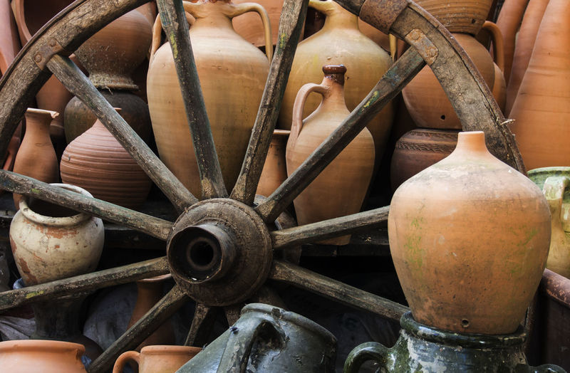 Wagon Wheel Amidst Pottery For Sale