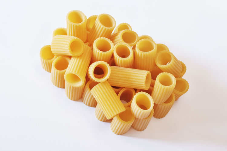 Italian pasta called rigatoni on a white background ,tube shaped pasta with ridges down their length , studio shot Curves Mediterranean Food Carbohydrate - Food Type Close-up Dry Food Food Gourmet Food Heap Italian Food Lifestyles No People Nutrition Pasta Raw Food Ridge Rigatoni Pasta Section Still Life Studio Shot Tastyfood Top View Of Food Tubes Uncooked Pasta White Background Yellow