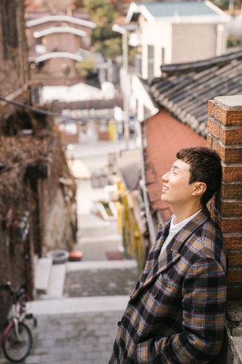 Side view of man standing on street against buildings