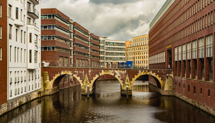 Bridge over river by buildings against sky