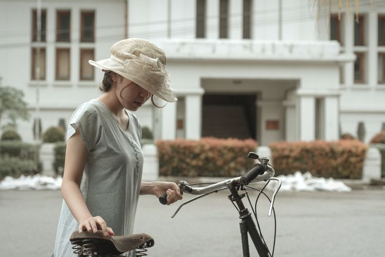 Woman wearing hat with bicycle on field