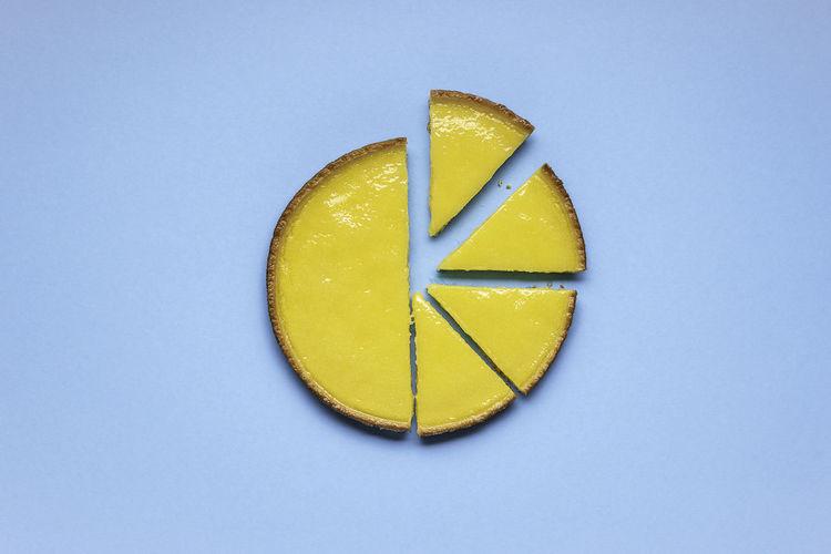 Directly above shot of lemon slice against blue background