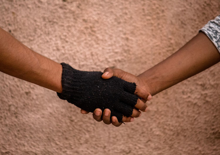 Cropped image of friends shaking hands against wall